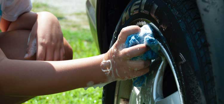 Kid washing a car tire