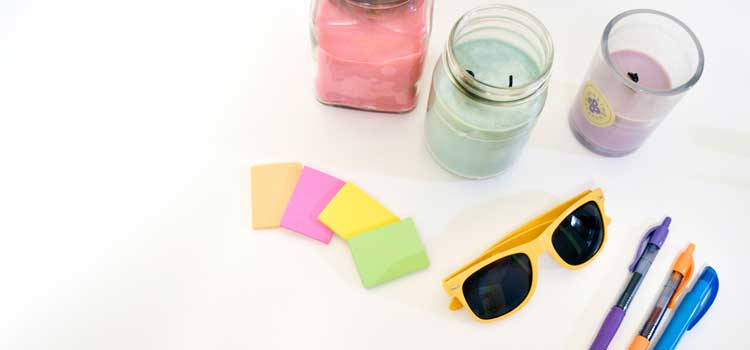 candles, sunglasses, and pens in a pile
