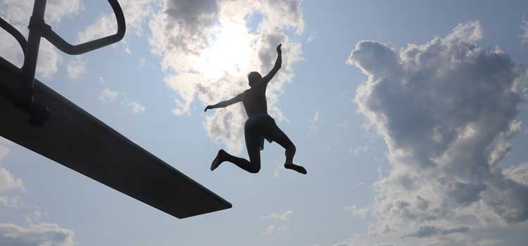 a kid jumping off a diving board