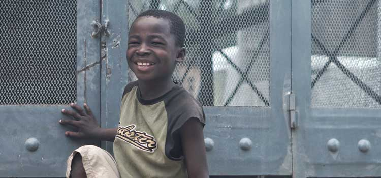 a boy smiling near a fence